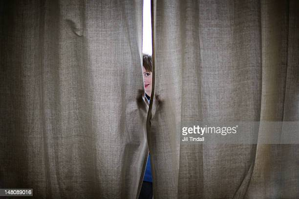 Young boy peeping through closed curtains
