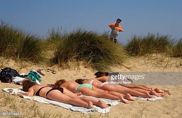 A young boy peers over a clump of vegetation to spy on four beautiful women who are all lying facedown in a sandy dune near the seaside resort of...
