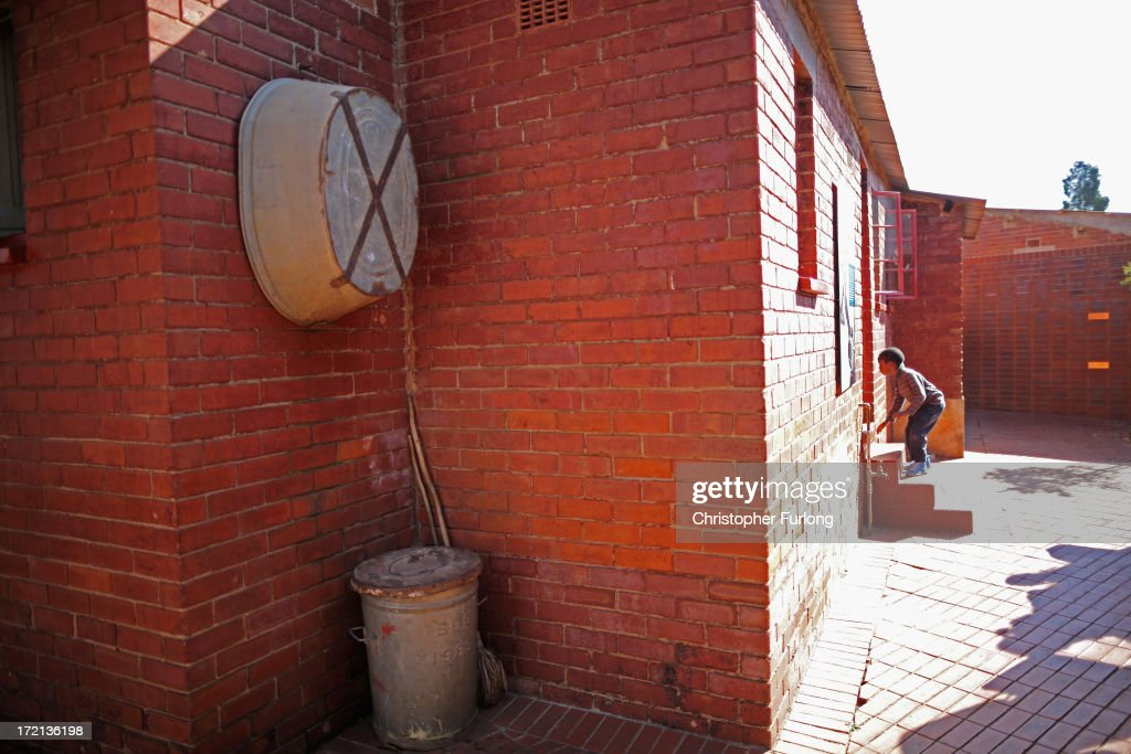 A young boy peers through the back door of the 'Mandela House' museum at 8115 in Vilakazi Street in the Orlando West section of Soweto Township on July 2, 2013 in Soweto, Johannesburg, South Africa. 8115 is the location of the first house owned by former South African President Nelson Mandela where he lived for 44 years from 1946 to 1990. The 'Mandela House', now a museum is managed by the Soweto Heritage Trust which has seen an increase in vistors both local and international since Mandela was hospitalized with a lung infection on June 8, 2013 and still remains in a critcal condition.