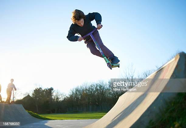 young boy performing stunt on micro scooter. - sporting term stock pictures, royalty-free photos & images