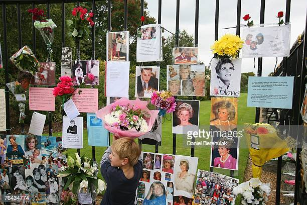 Young boy places a bouquet of flowers on the fence in tribute of the late Diana, Princess of Wales at Kensington Palace on August 31, 2007 in London,...