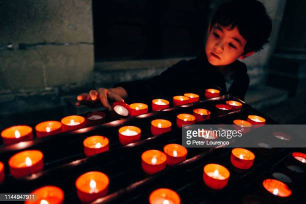 Young boy placing a prayer candle