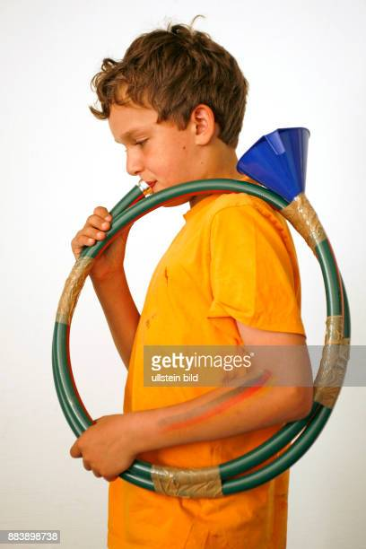 young boy playing a selfmade horn / child / children / childhood / musical instrument
