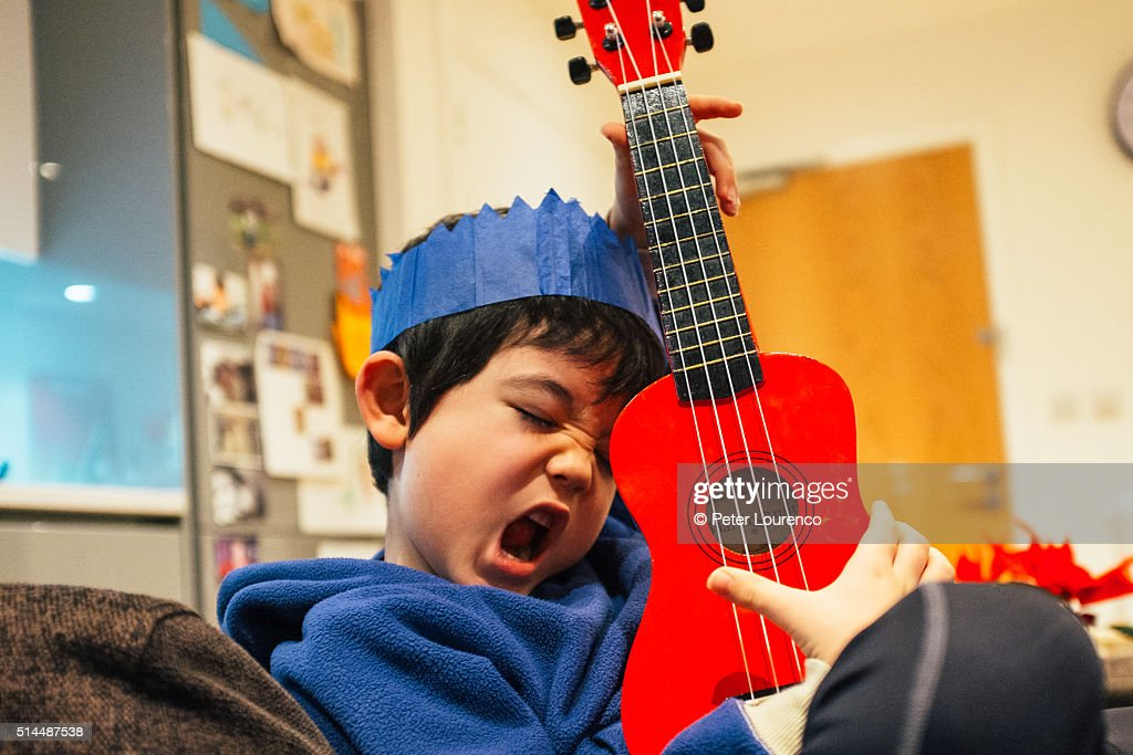Young boy playing a small guitar : Stock Photo