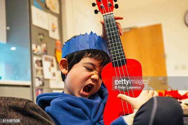 Young boy playing a small guitar