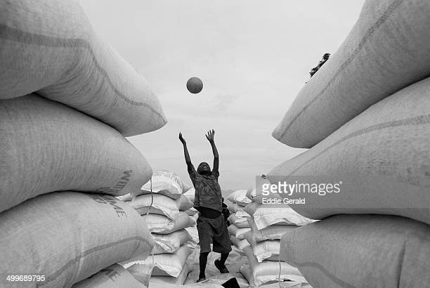 CONTENT] Young boy playing amid sacks of food during UN WFP Food distribution in North Kivu Congo DRC