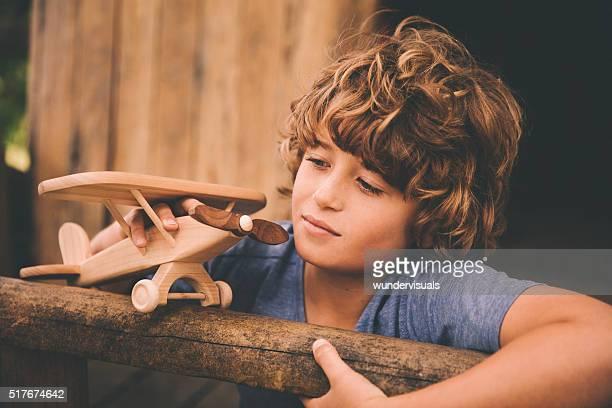 Jeune garçon jouant et à la rêverie avec son avion jouet en bois