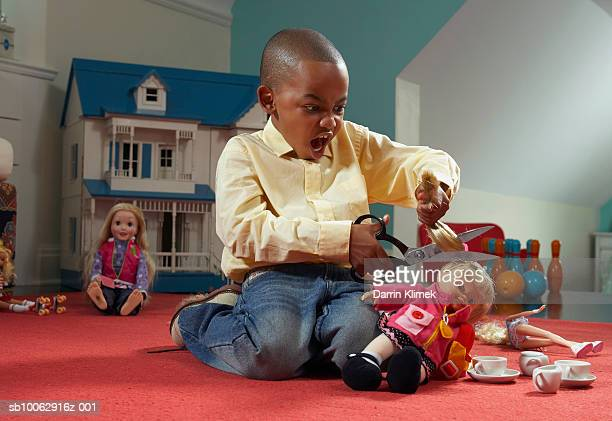 young boy (6-7 years) playing at home, kneeling and cutting dolls hair with scissors, dollhouse in background - destruição - fotografias e filmes do acervo
