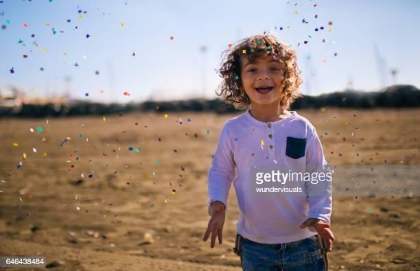 Jonge jongen spelen op het strand met confetti