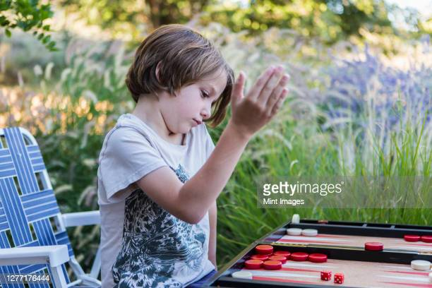 a young boy playing backgammon outdoors in a garden. - backgammon stock pictures, royalty-free photos & images