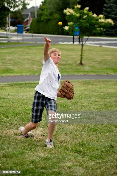 Young boy playing baseball in suburb park.