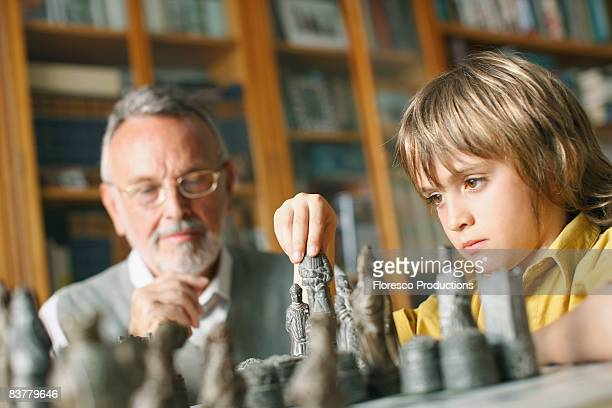 Young boy playing chess with grandfather
