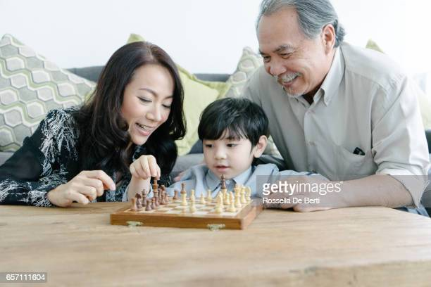 Young boy playing chess with grandparents