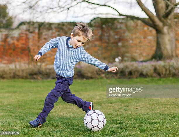 young boy playing football in the garden - long sleeved stock photos and pictures