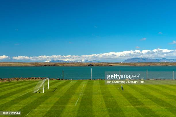 young boy playing football on pitch beside the sea - blue balls pics stock pictures, royalty-free photos & images