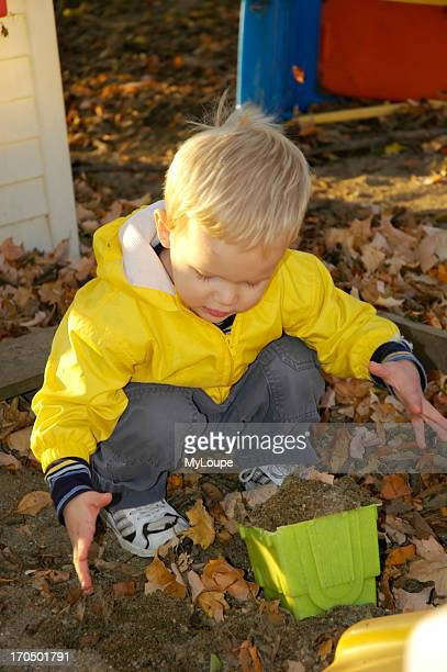 Young Boy Playing In A Sandbox On A Cool Autumn Day