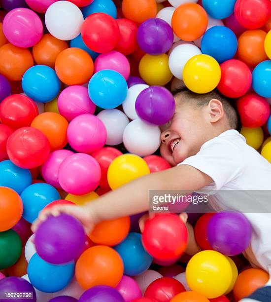 Young boy playing in colorful ball pit