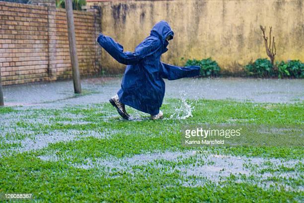 young boy playing in rain - extra groot stockfoto's en -beelden