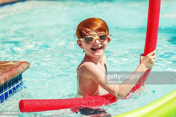 Young boy (6-7) playing in swimming pool