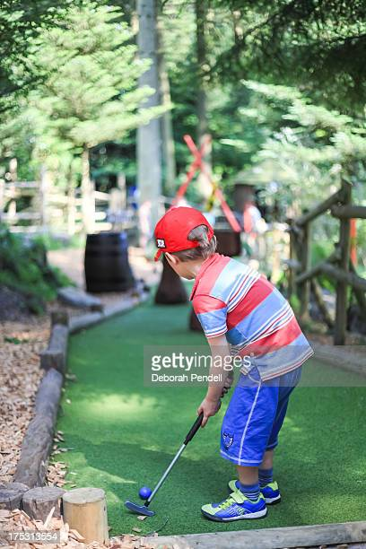 young boy playing mini golf or crazy golf - miniature golf stock photos and pictures