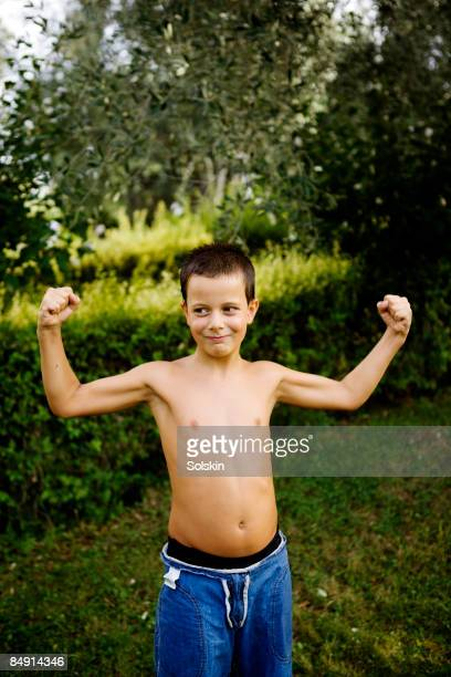 young boy playing muscle man