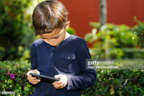 A young boy playing on a mobile phone