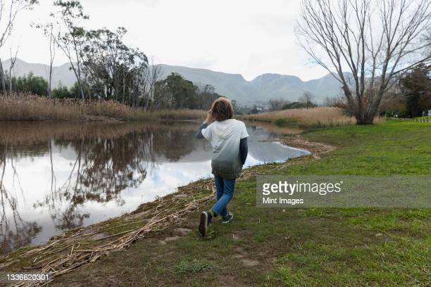 young boy playing on a river bank, flat calm water, and wide open spaces on the klein river estuary. - klein bildbanksfoton och bilder