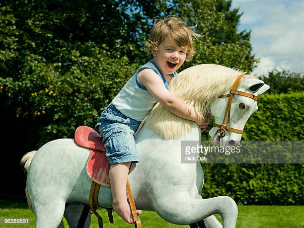 A young boy playing on a rocking horse