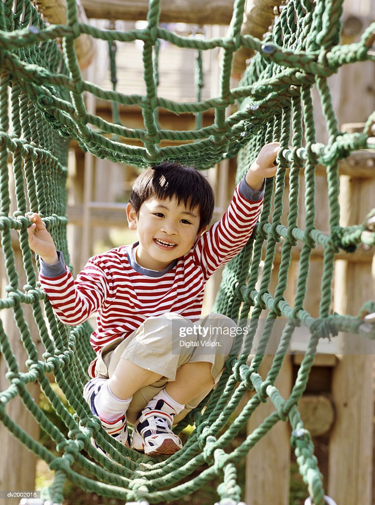 Young Boy Playing on Climbing Ropes in an Adventure Playground : Stock Photo