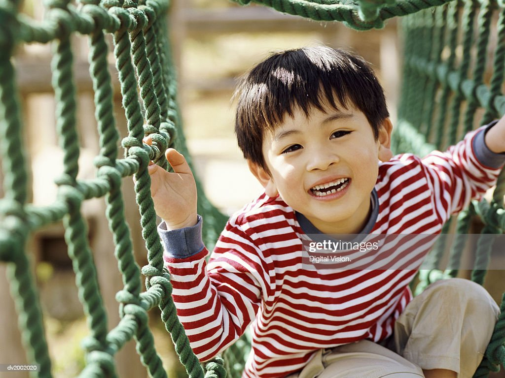 Young Boy Playing on Climbing Ropes : Stock Photo