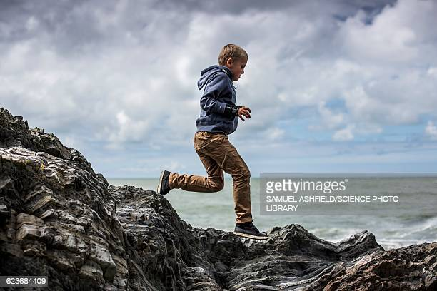 Young boy playing on rocks on beach