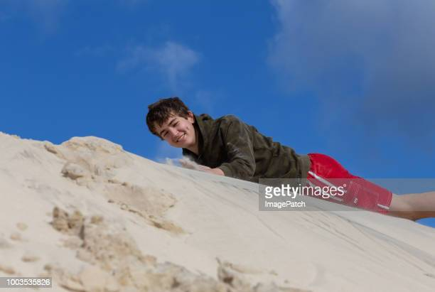 Young boy playing on sand dunes on a winter's day