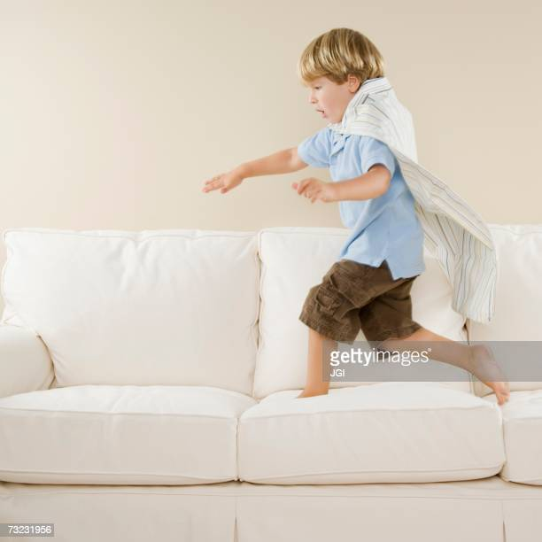 Young boy playing on sofa
