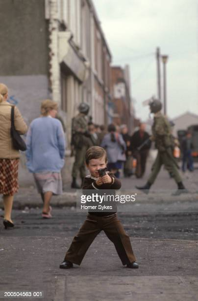 A young boy playing on the streets of Belfast with a toy rifle He fires at the pretend enemy British soldiers on parole in the background during the...