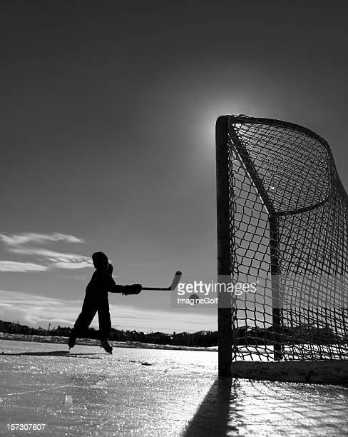 young boy playing outdoor ice hockey - ice hockey stick stock pictures, royalty-free photos & images