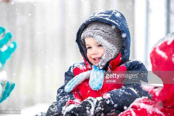 young boy playing outside in snow storm blizzard - red coat stock pictures, royalty-free photos & images