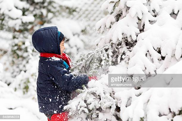 Young boy (4-5) playing outside in winter