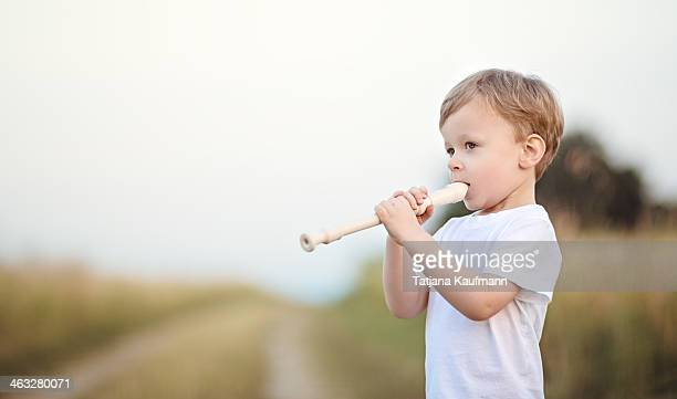 Young boy playing recorder outside in summer