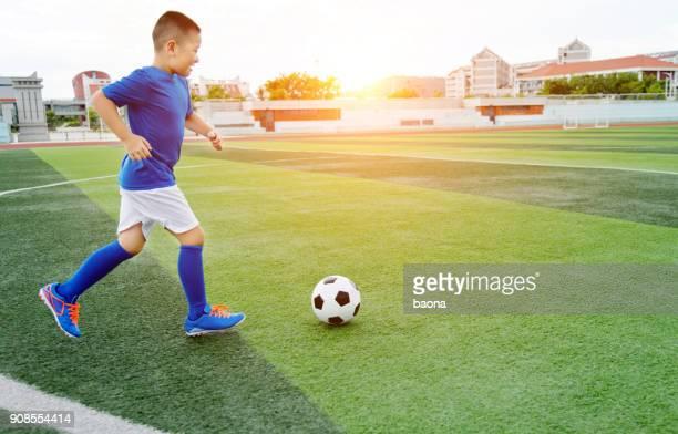 menino jogando bola de futebol no campo - chutar - fotografias e filmes do acervo