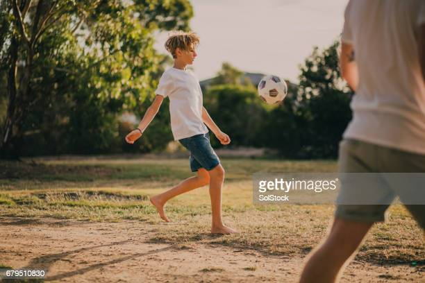 Young Boy Playing Soccer in the Park