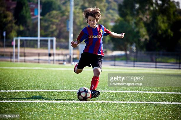Young boy playing soccer on green synthetic