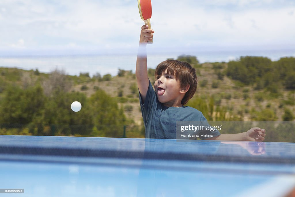 Young boy playing table tennis outdoors : Stock Photo