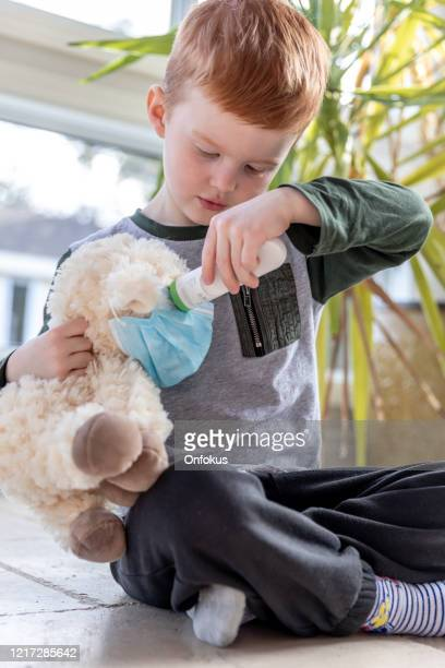 young boy playing taking infrared temperature of his sick peluche wearing a mask. - infrared thermometer stock pictures, royalty-free photos & images