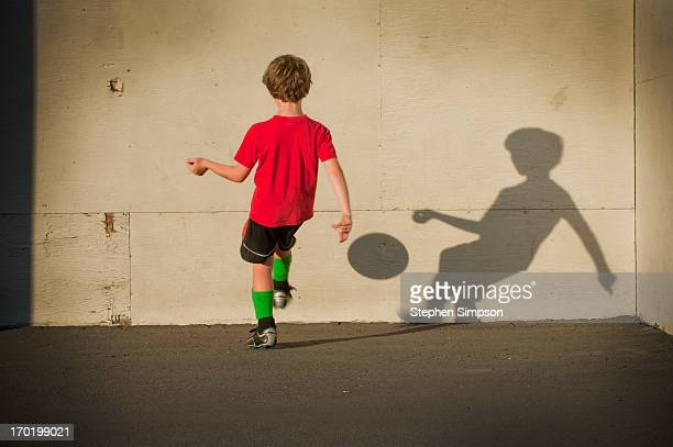 young boy playing 'wall ball' with his shadow