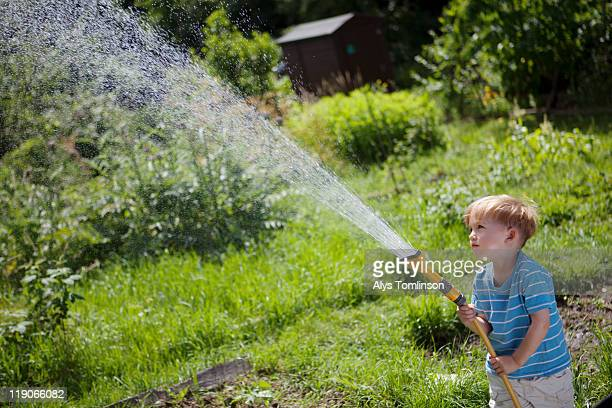 Young boy playing with a hose outdoors