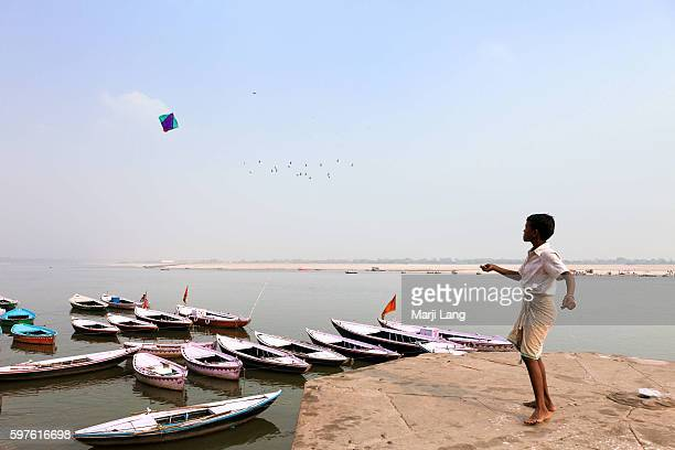 Young boy playing with a kite by the Ganges river in Varanasi