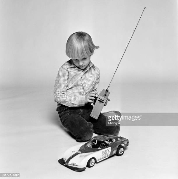 A young boy playing with a remote control car December 1980
