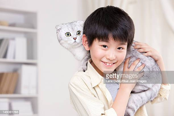 Young boy playing with a Scottish Fold cat