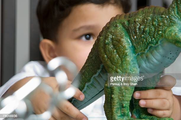 young boy playing with a toy dinosaur - palaeontology stock pictures, royalty-free photos & images