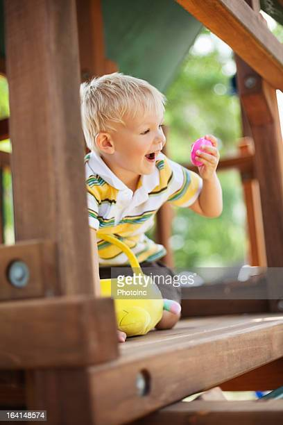 A young boy playing with a toy in a wooden playhouse